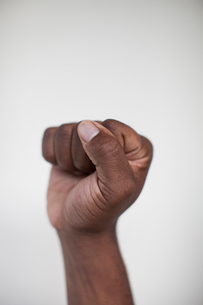 Cropped hand of man clenching fist against white wall at homeの写真素材 [FYI03705878]