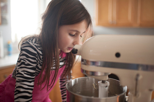 Girl looking at mixer in kitchen at homeの写真素材 [FYI03705899]