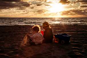Rear view of siblings sitting on sand at beach against sky during sunsetの写真素材 [FYI03706053]
