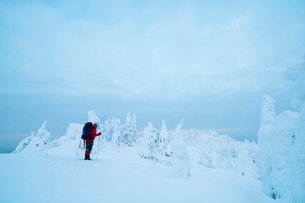Side view of hiker standing on snow covered fill against cloudy skyの写真素材 [FYI03706217]