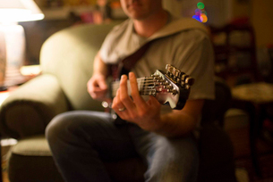 Midsection of man playing guitar while sitting on armchair at homeの写真素材 [FYI03706375]