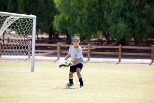 Girl practicing soccer in playgroundの写真素材 [FYI03706402]