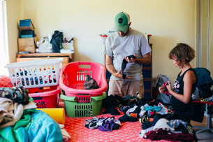 Father and daughter folding laundry at homeの写真素材 [FYI03706414]