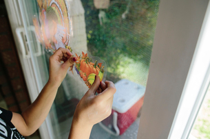 Cropped hands of girl sticking fruits label on window glass at homeの写真素材 [FYI03706442]