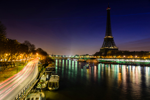 Light trails on bridge over river by Eiffel Tower at nightの写真素材 [FYI03706526]
