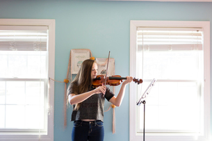 Woman playing violin while standing by window at homeの写真素材 [FYI03706884]