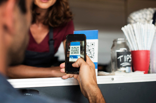 Cropped image of customer paying through smart phone at food truckの写真素材 [FYI03706993]