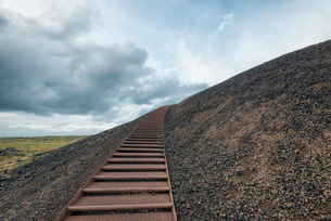 Metallic steps on mountain against cloudy skyの写真素材 [FYI03707994]