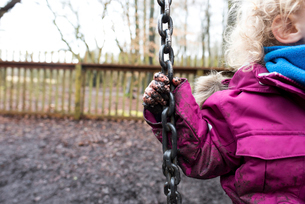 Cropped image of girl with muddy hand playing on swing at park during rainy seasonの写真素材 [FYI03708050]