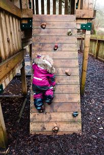 Rear view of girl rock climbing at park during rainy seasonの写真素材 [FYI03708052]