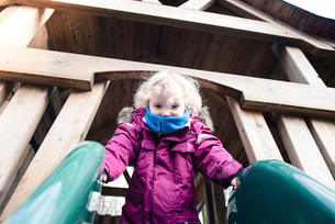 Low angel view of girl on slide at park during rainy seasonの写真素材 [FYI03708053]