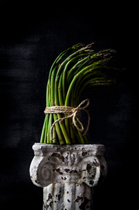 Bunch of asparagus on old pedestal against black backgroundの写真素材 [FYI03708081]