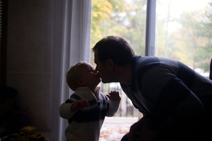 Father and son kissing while standing by window at homeの写真素材 [FYI03708119]