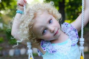 Portrait of girl sitting on swing in playgroundの写真素材 [FYI03708129]