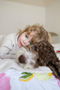 Portrait of happy girl relaxing with dog on bed at homeの写真素材 [FYI03708130]