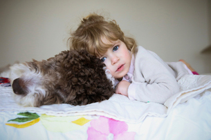 Portrait of girl relaxing with dog on bed at homeの写真素材 [FYI03708131]