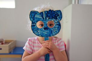 Portrait of girl holding cat mask while standing at homeの写真素材 [FYI03708137]