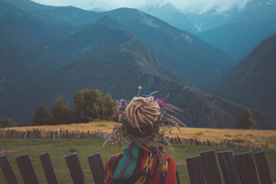 Rear view of woman with dread locks hair bun standing on field against mountainsの写真素材 [FYI03708143]