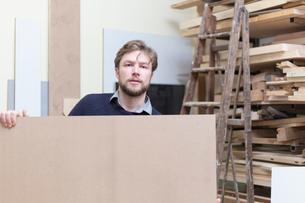 Portrait of carpenter holding wooden planks in workshopの写真素材 [FYI03708195]