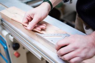 Cropped hands of carpenter measuring wooden planks at workshopの写真素材 [FYI03708200]
