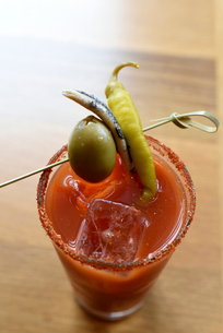 Close-up of drink garnished with olive and chili in drinking glass on wooden tableの写真素材 [FYI03708289]