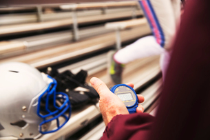 Cropped hand of American football coach holding stopwatch at stadiumの写真素材 [FYI03708434]
