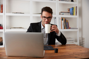 Businessman holding coffee mug while using laptop at table in home officeの写真素材 [FYI03708447]