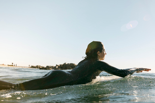 Side view of female surfer lying on surfboard in sea against clear skyの写真素材 [FYI03708512]