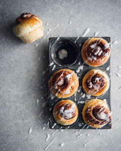 Overhead view of cream splashed on cinnamon rolls in baking trayの写真素材 [FYI03708869]