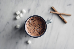Overhead view of frothy hot chocolate in mug with marshmallows and cinnamon on tableの写真素材 [FYI03708885]