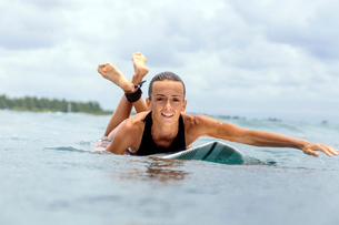 Portrait of woman surfboarding against cloudy skyの写真素材 [FYI03709150]