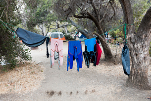 Wetsuits drying on clothesline at campsiteの写真素材 [FYI03709217]