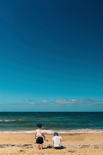 Rear view of siblings playing at beach against blue sky during sunny dayの写真素材 [FYI03709259]