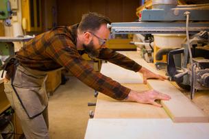 Side view of carpenter working in workshopの写真素材 [FYI03709347]