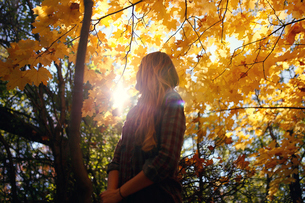 Low angle view of woman standing by autumn tree at parkの写真素材 [FYI03709468]