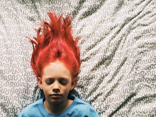 Overhead view of boy with redhead sleeping on bed at homeの写真素材 [FYI03709530]