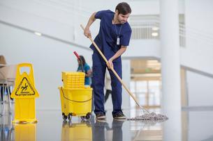 Male worker cleaning hospital floorの写真素材 [FYI03709763]