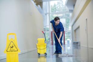 Male worker cleaning floor at hospital corridorの写真素材 [FYI03709766]
