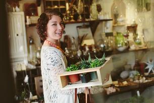 Portrait of happy customer carrying plants in crate at garden centerの写真素材 [FYI03709988]