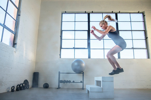 Full length of athlete jumping on wooden seat in gymの写真素材 [FYI03710468]