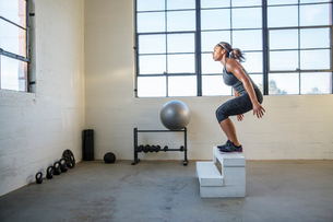 Female athlete jumping on wooden seat in gymの写真素材 [FYI03710473]
