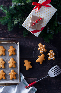 High angle view of gingerbread man with Christmas presents and utensils on tableの写真素材 [FYI03710676]
