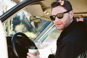 Handsome man in sunglasses holding disposable cup while sitting in carの写真素材 [FYI03710687]