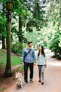Happy couple holding hands and walking on footpath with dog at parkの写真素材 [FYI03710710]