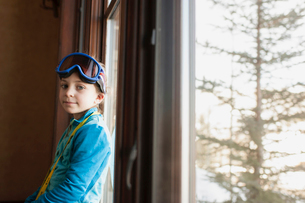 Portrait of girl with swimming goggles standing by window at homeの写真素材 [FYI03710805]