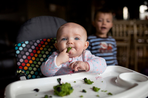 Baby girl eating food on high chair while brother standing in backgroundの写真素材 [FYI03710871]