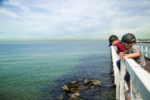 Brothers looking at sea while standing on railing of pier against cloudy skyの写真素材 [FYI03710942]