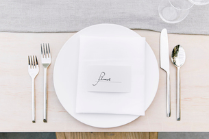 Overhead view of silverware by plate with text on dinning tableの写真素材 [FYI03711014]