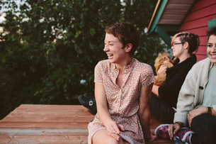 Happy friends relaxing on rooftopの写真素材 [FYI03711272]