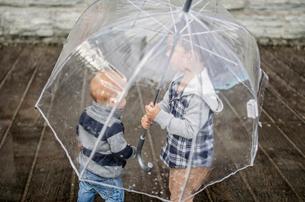 Brothers below transparent umbrella standing on walkway during rainy seasonの写真素材 [FYI03711277]
